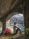 Italy, Hiker sitting under bridge, looking to Lago di Salarno - LAF02140