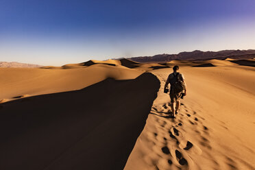 USA, Californien, Death Valley, Death Valley National Park, Mesquite Flat Sand Dunes, man walking on dune - FCF01520