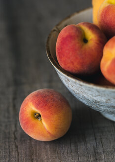 High angle close-up of peaches in bowl on wooden table - CAVF52776