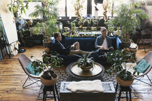 Homosexual couple relaxing while sitting on sofa amidst potted plants at home - CAVF52815