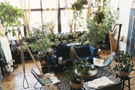 Loving gay couple amidst potted plants at home - CAVF52821