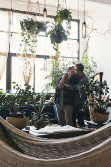Gay couple kissing while standing against potted plants at home - CAVF52824
