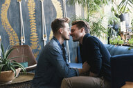 Side view of gay men romancing at home - CAVF52827