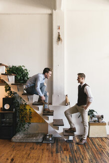 Gay man with hand in pocket looking at boyfriend wearing shoe on stairs - CAVF52833