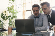 Homosexual gay couple using laptop computer together at home - CAVF52845