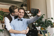 Smiling gay man taking selfie with smart phone while boyfriend kissing him at home - CAVF52848