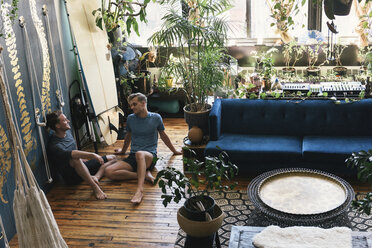 High angle view of gay men sitting on hardwood floor at loft apartment - CAVF52854