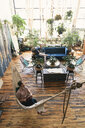 High angle view of gay man relaxing in hammock while boyfriend sitting on sofa against potted plants at home - CAVF52857