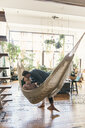 Full length of gay man kissing boyfriend lying in hammock at home - CAVF52860