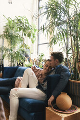 Loving Gay couple relaxing while sitting on sofa against potted plants at home - CAVF52863