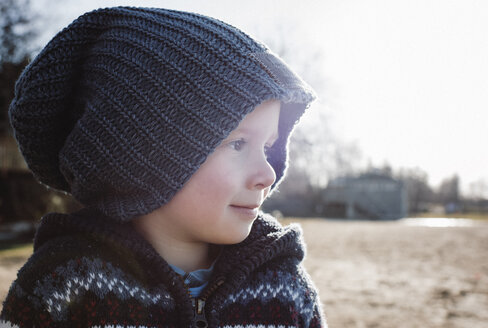 Close-up of thoughtful boy looking away while standing on field against clear sky - CAVF52869