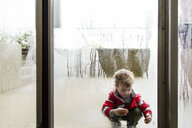 Playful boy wearing raincoat seen through wet window - CAVF52895