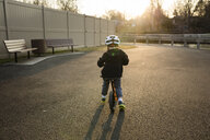 Rear view of boy wearing cycling helmet while riding bicycle on road during sunset - CAVF52898