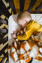 Overhead view of cute baby boy sleeping in crib at home - CAVF52901