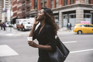 Businesswoman with coffee talking on smart phone while walking on city street - CAVF52970