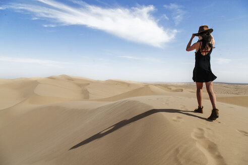 Rear view of young woman wearing hat while walking on sand dune at desert against sky during sunny day - CAVF52985