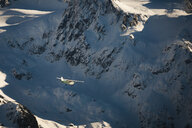 Aerial view of aircraft flying by snowcapped mountain at Garibaldi Park - CAVF52994
