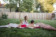 Siblings relaxing on blanket at backyard - CAVF53027