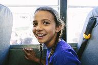 Portrait of happy girl traveling in bus - CAVF53050