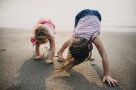 Playful sisters bending on sand at beach against sky - CAVF53053