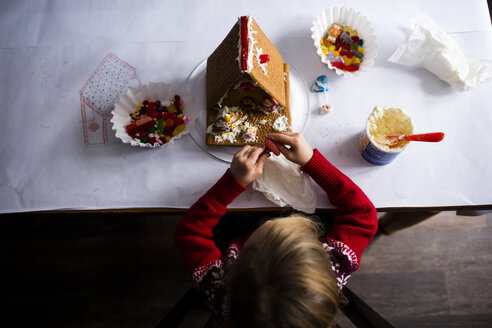 Overhead view of girl making gingerbread house on table at home - CAVF53056