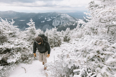 Hiker with backpack walking in forest during winter - CAVF53089