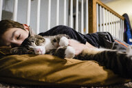 Boy with cat sleeping on bed at home - CAVF53095