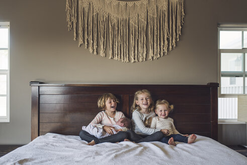 Cheerful sisters with baby girl sitting on bed at home - CAVF53116