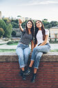 Full length of happy female friends taking selfie with instant camera while sitting on retaining wall at park - CAVF53134