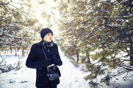 Young man with vintage camera wearing black warm clothing amidst forest during winter - CAVF53164
