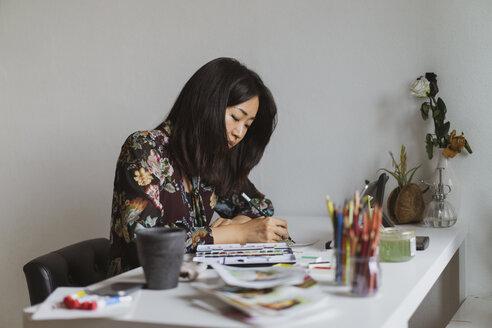 Illustrator drawing at work desk in an atelier - AFVF01935