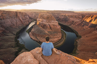 USA, Arizona, Colorado River, Horseshoe Bend, young man sitting on viewpoint - KKAF02843