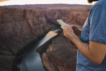 USA, Arizona, Colorado River, Horseshoe Bend, young man on viewpoint using smartphone - KKAF02852