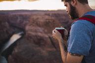 USA, Arizona, Horseshoe Bend, Young man holding red cup - KKAF02855