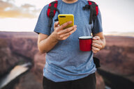 Young man holding red cup and using smartphone - KKAF02858
