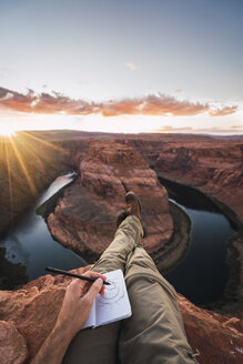 USA, Arizona, Colorado River, Horseshoe Bend, young man on viewpoint, painting - KKAF02861