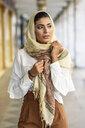 Spain, Granada, young muslim woman wearing hijab in urban city background - JSMF00543