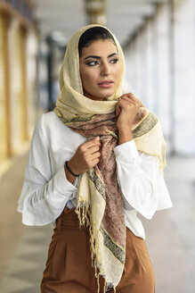Spain, Granada, young muslim woman wearing hijab in urban city background - JSMF00543