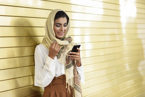 Spain, Granada, young Arab tourist woman wearing hijab, using smartphone - JSMF00546