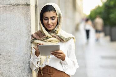 Spain, Granada, young muslim woman wearing hijab using tablet outdoor - JSMF00549