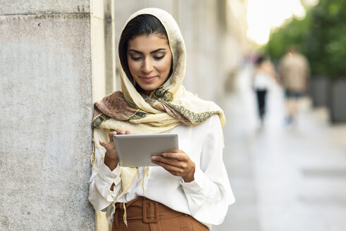 Spain, Granada, young muslim woman wearing hijab using tablet outdoor - JSMF00549