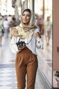 Spain, Granada, young Arab tourist woman wearing hijab, using fotocamera during shopping in the city - JSMF00552
