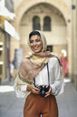 Spain, Granada, young Arab tourist woman wearing hijab, using camera during sightseeing in the city - JSMF00555