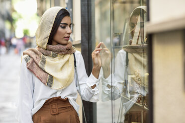 Spain, Granada, young muslim tourist woman wearing hijab looking at shop windows on a shopping street - JSMF00558