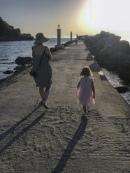 Greece, Parga, mother and daughter at the pier at sunset - PSIF00143