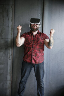 Happy bearded man wearing VR glasses - REAF00461
