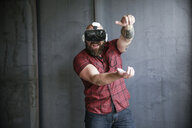 Excited bearded man wearing VR glasses - REAF00467