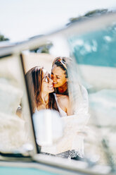 Lesbian couple doing a road trip, kissing and embracing in nature - OCMF00079