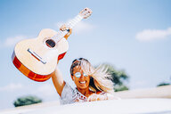 Happy young woman holding her guitar aloft, standing in her van on a road trip - OCMF00082