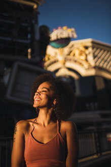 USA, Nevada, Las Vegas, portrait of happy young woman in the city at night - KKAF02892